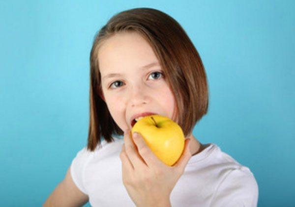 Дівчинка гризе яблуко