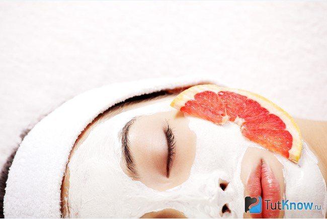 Дівчина лежить з часточкою грейпфрута на обличчі