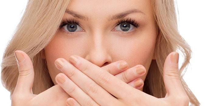 Дівчина прикриває рот руками
