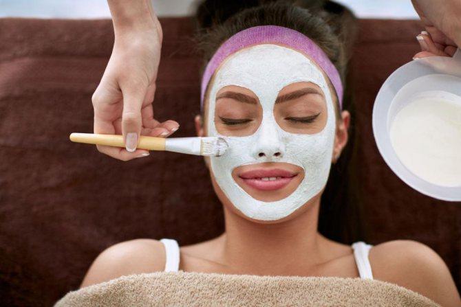 Глиняна маска на обличчі у дівчини