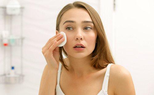 Красива дівчина очищає обличчя ватним диском
