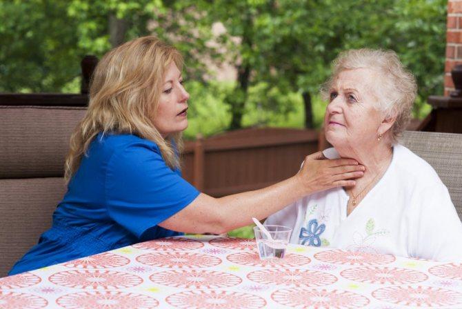 Медсестра, яка оцінює горло старшої жінки і ковтає після удару, торкнулася мову.