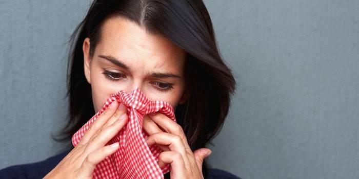 Жінка тримає хустку у носа